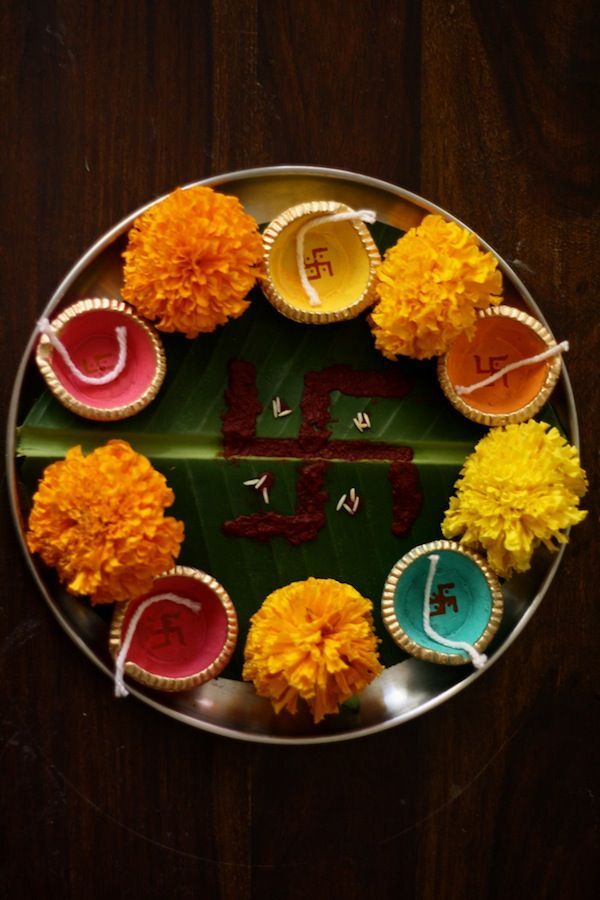 A plate decorated with Diya's and Marigold Flowes for Aarti.