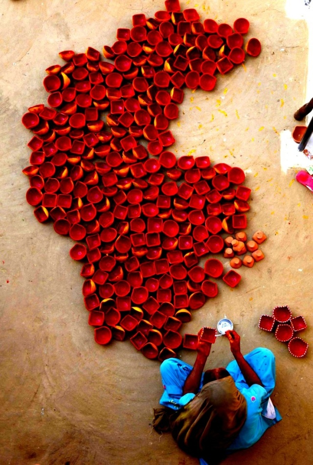 A women painting the diya's.