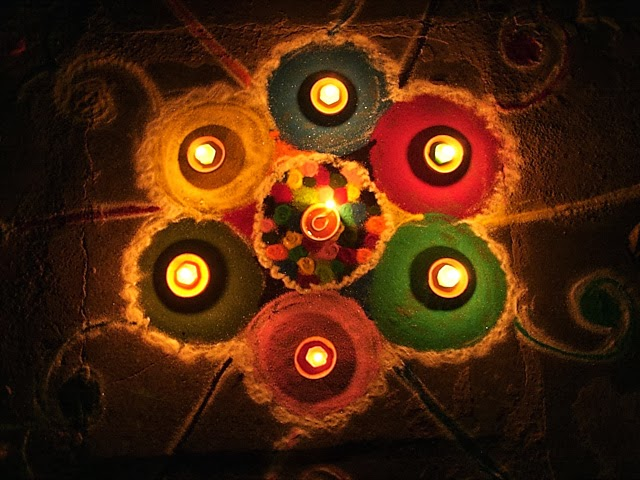 A Rangoli design with diya's on top.